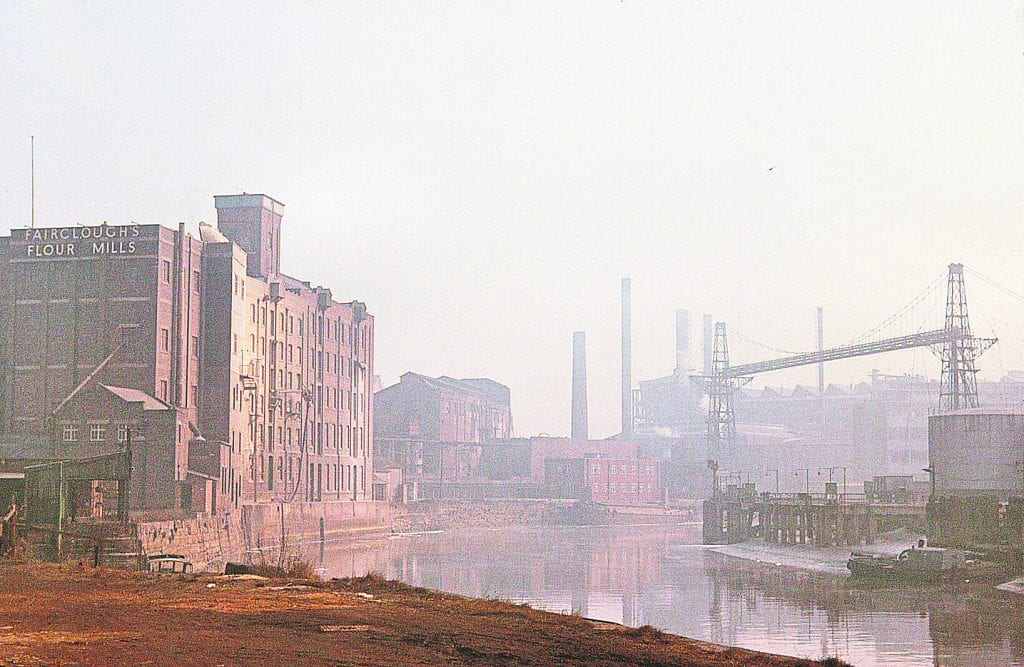 Barges and the ferry at Joseph Crosfield & Sons' Bank Quay wharves on the River Mersey in 1960 with the original 1905-built Warrington Transporter Bridge in the background. The later bridge is just around the bend.
