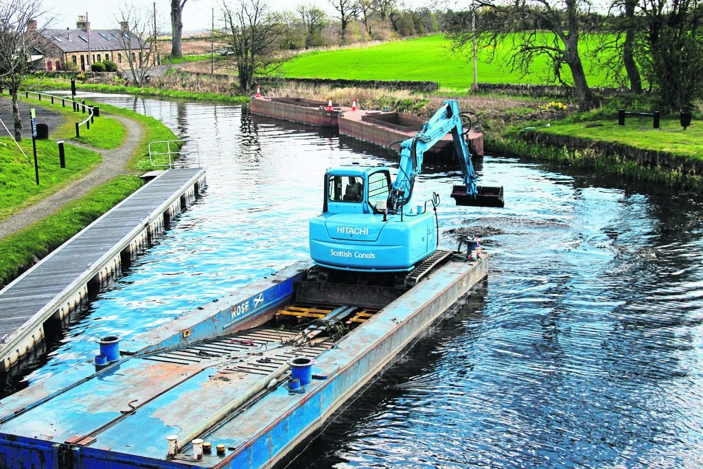 The pontoon with digger aboard in action as the 'pans' sit by the bank.