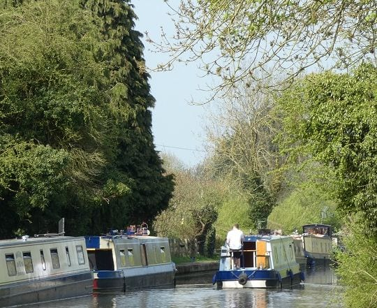 narrowboats moored along towpath