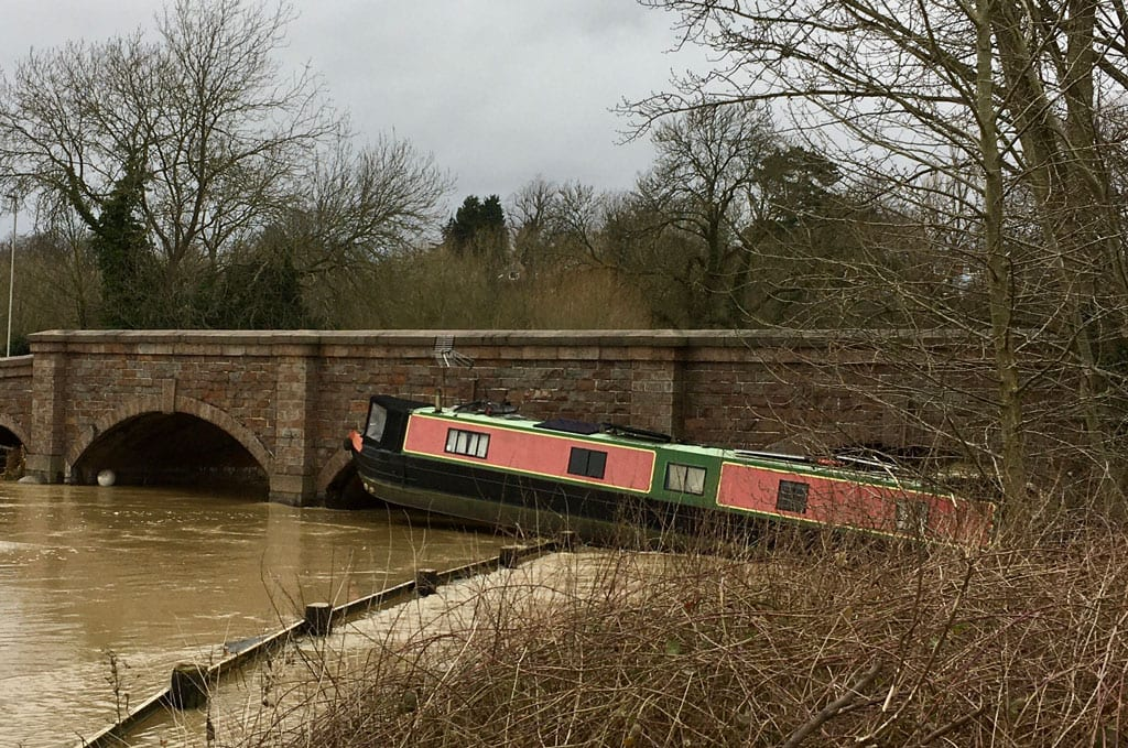Capsized narrow boat on the edge of the River Soar.