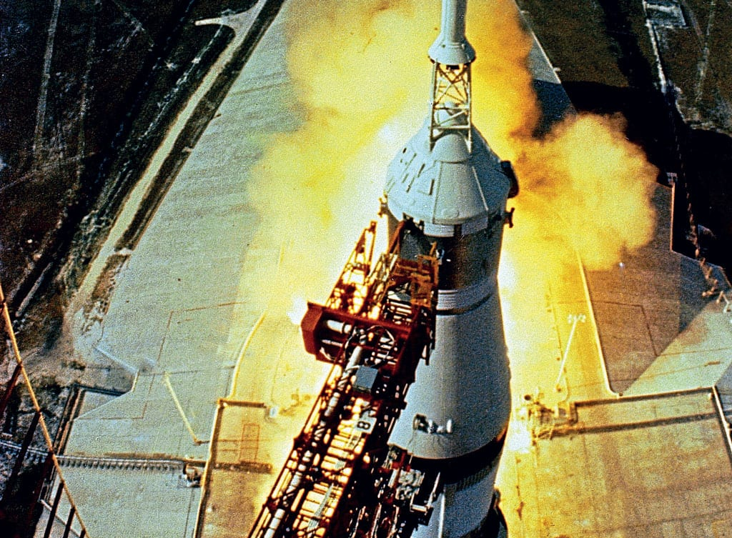 Seconds before lift-off, a fish-eye lens camera high up on the Launch Umbilical Tower casts a dramatic view of the five F-1 engines running up to full thrust before release. Note the white boost protective cover (BPC) supporting the launch escape system (LES) encapsulating the Command Module. (NASA)