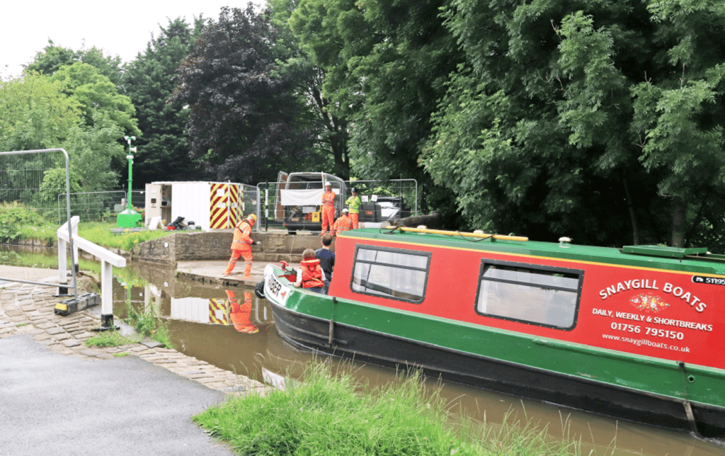 A hireboat passes contractors getting ready to replace the Gawflat swing bridge in Skipton.