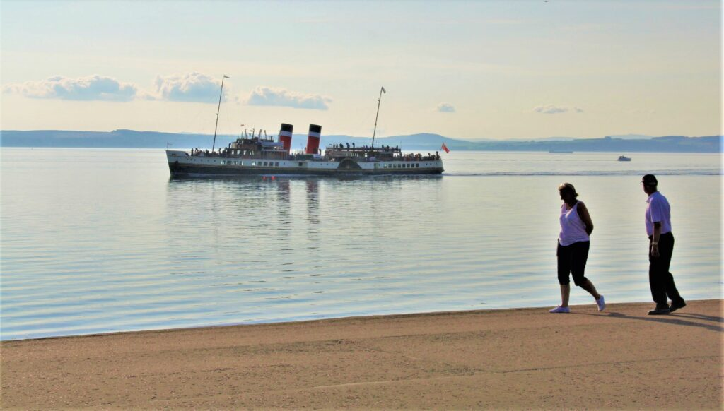 A couple on the shore watch Waverley as she makes for Largs Pier on 22 August. Hugh Dougherty
