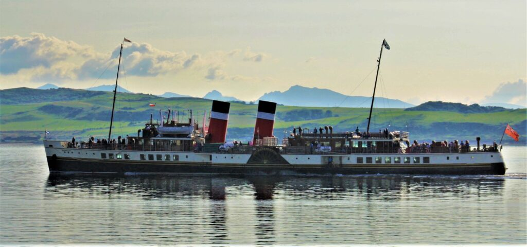 Sailing serenely, Waverley approaches Largs Pier, with Cumbrae and the mountains of Arran behind, to decant a full load of passengers on 22 August. Hugh Dougherty