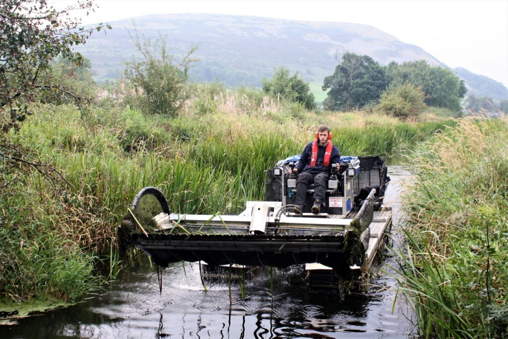James Ormrod is at the controls of a Truxor amphibious tractor, which each year clears away hundreds of tonnes of unwanted weeds and reeds from the waterway.