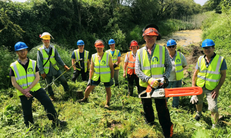 Branch chairman Dave Maloney, front with chainsaw and fellow volunteers clearing the former Wilts & Berks Canal at Green Lane Farm east of Chippenham. PHOTO: JUSTIN GUY