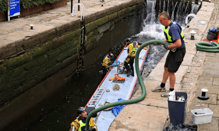 Pipework being passed down into Lock 92 on the Rochdale Canal to pump out water from the sunken narrowboat